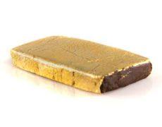 Una tableta de CBD hachís cbd cubiertas con un brillo dorado